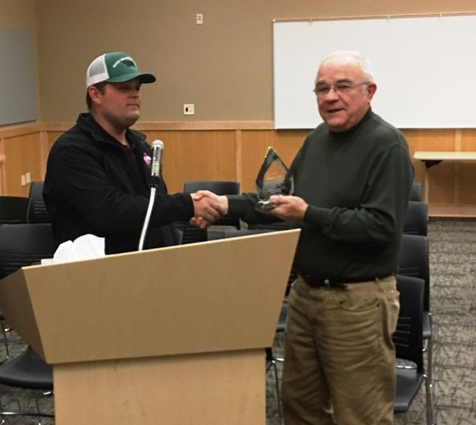 Commissioner Scott Vejraska presenting plaque